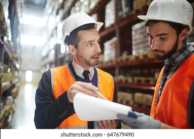 Supervisor in helmet pointing at document while talking to one of managers