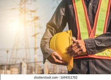 Supervisor holding white hat safety hard hat sunlight background