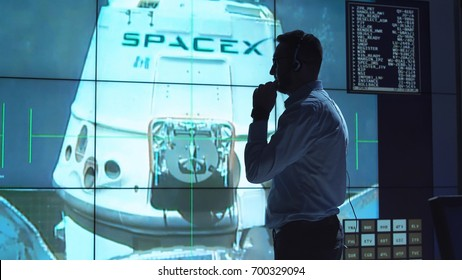 Supervisor man standing near big screen in space flight control center watching satellite. Elements of this image furnished by NASA.