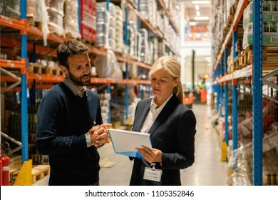 Supervisor taking inventory check with warehouse manager