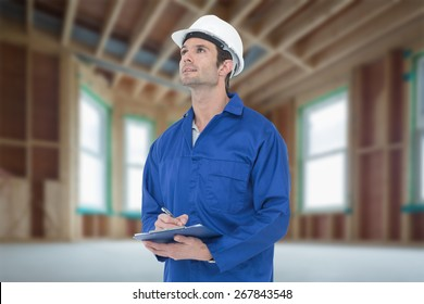 Supervisor writing notes on clip board against house under construction