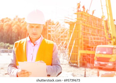 Supervisor writing on clipboard at construction site