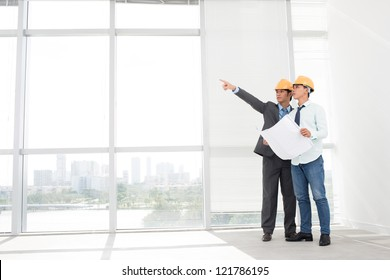 Supervisors in hardhats inspecting empty office premises