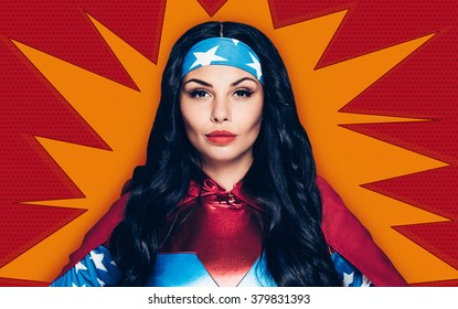 Superwoman. Portrait of beautiful young woman in superhero costume looking at camera while standing against red background