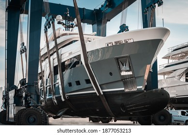 Superyacht being hauled out of the water with big cranes into dry shipyard storage
