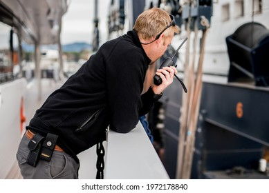 Superyacht crew member coordinating a vessel haul out on travel lift with handheld radio