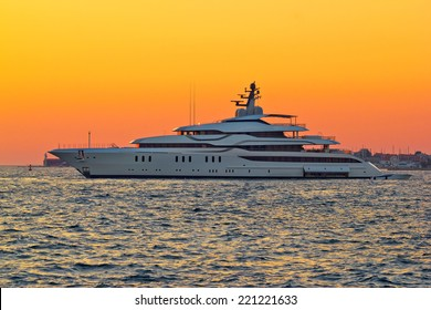 Superyacht on yellow sunset side view