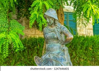 SUPETAR, CROATIA - September 16, 2014 Bronze statue of a girl in a green yard, work of Croatian sculptor Ivan Rendic.