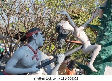 SUPHAN BURI, THAILAND, JAN 01 2018, Naked sinners is tortured on a thorny tree with sharp spikes. A scene from Buddhist hell. Torture of sinful people, afterlife.