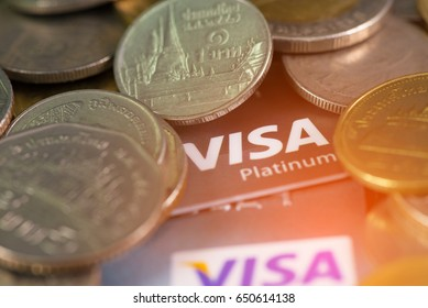 Suphanburi, Thailand - 22 May 2017 : Pile of VISA card, credit cards with coins and money on the table. business concept. shallow focus, soft tone.