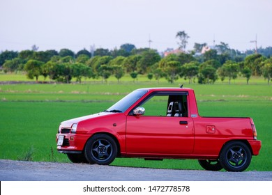 SUPHANBURI, THAILAND - MAY 13, 2018: Photo of Vintage Daihatsu Mira small pickup truck parking isolated forest background.