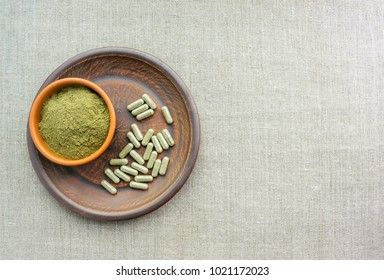 Supplement kratom green capsules and powder on brown plate. Herbal product alt-medicine kratom is  opioid. Home alternative pain remedy, opioid addiction, dangerous painkiller, overdose. Copy space