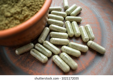 Supplement kratom green capsules and powder on brown plate. Herbal product alt-medicine kratom is  opioid. Home alternative pain remedy, opioid addiction, dangerous. Close up. Selective focus