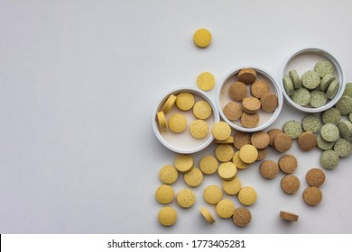 Supplements are scattered on the surface of the table in the corner. White background. Vitamins and food additives have natural plant components and healthy nutrients. Vegetarian pills.