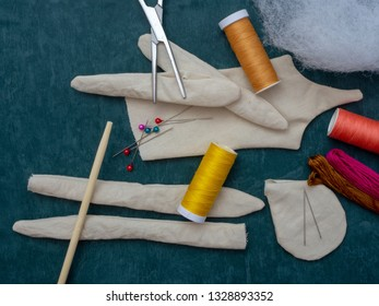 Supplies for making a rag doll on a green background. Top view.
