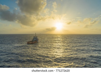 Supply boat over sea with sunset and sky background
