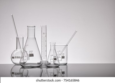 Supply of empty laboratory glass chemical containers on glass table. Representation in gray tones. Horizontal composition. Front view