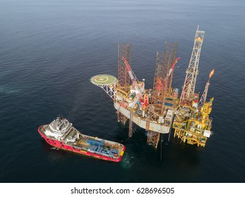 Supply Vessel Alongside Offshore Jack Up Drilling Rig Over The Production Platform in The Middle of The Sea