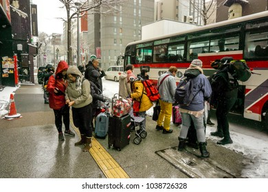Supporo, Hokkaido, Japan 12 February 2018 : Group of Chinese tourist waiting for bus to travel to different cities as the snow began to fall again.