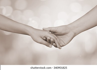 support assistance human hands reaching touch together on blurred bokeh tan background for helping concept.