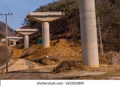 Support columns for new highway at rural mountainside construction site.