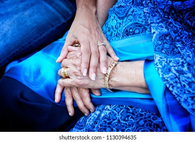 Support concept. Young hand holding wrinkled hands of Indian woman, dressed in traditional blue sari.
