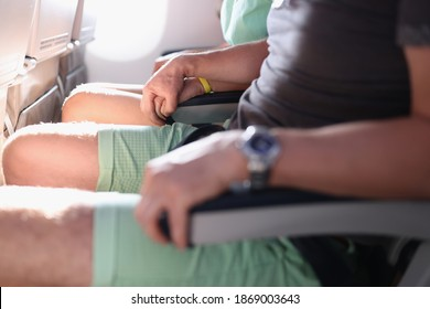Support of fear of heights, and fear of flying in passenger seats in cabin. Stress when traveling by plane. Man hold woman hand in passenger seats in aircraft cabin.