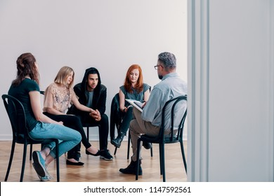 Support group sitting in a circle and talking to a psychiatrist