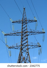 Support of a line of high-voltage electricity transmissions on a background of the blue sky,