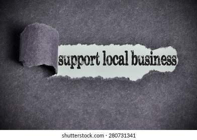 support local business word under torn black sugar paper.