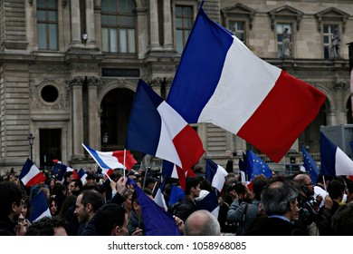 Supporters of French presidential election candidate Emmanuel Macron wave French national flags as they celebrate in front of the Pyramid at the Louvre Museum in Paris on May 7, 2017.