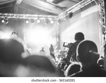 Supporters recording at concert, black and white, noise