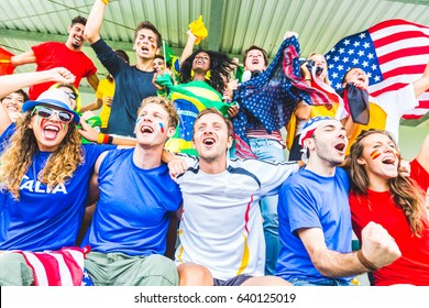 Supporters at stadium coming from different countries. Group of people enjoying sport match all together, with flags and colourful tshirts
