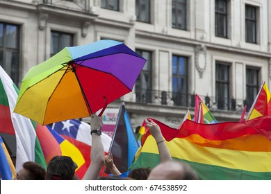Supporters wave flags an an unbrella at an LGBT gay pride march in London