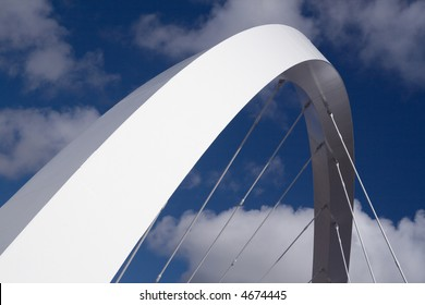 The supporting arch of the Clyde Arc bridge in Glasgow, Scotland, against blue sky and clouds