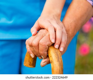 Supporting hand from doctor for elderly with parkinson's disease.