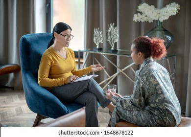 Supporting military woman. Asian psychoanalyst wearing glasses supporting young military woman