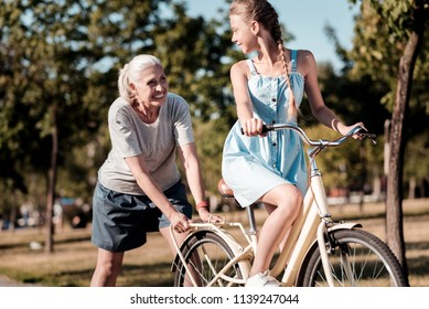 Supporting you. Smiling woman expressing positivity and standing behind bicycle while looking at her grandchild
