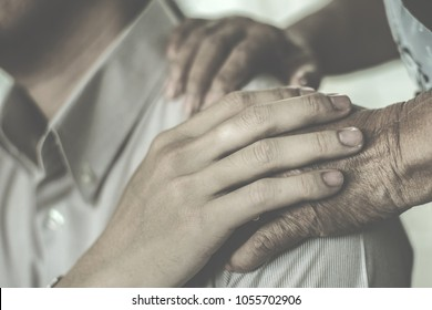 Supportive hands of elder try to cheer up a man