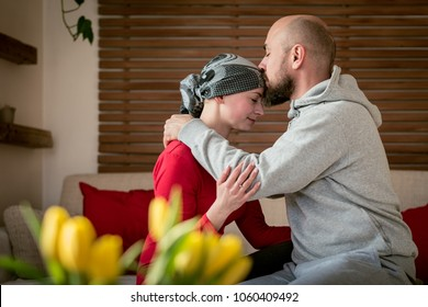 Supportive husband kissing his wife, cancer patient, after treatment in hospital. Cancer and family support concept.