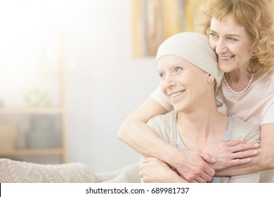 Supportive older woman hugging her friend struggling with cancer