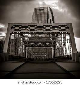 The supports of the walking bridge in downtown Nashville with a tall skyscraper in the background