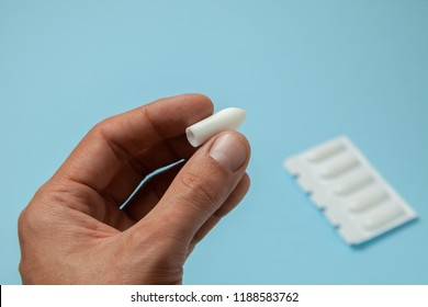 Suppository for anal or vaginal use in the hands of a man. Candles for treatment of hemorrhoids, temperature, thrush, inflammation
