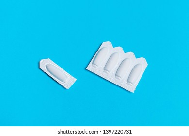 suppository on a blue background, for the treatment of hemorrhoids, vaginal candidiasis