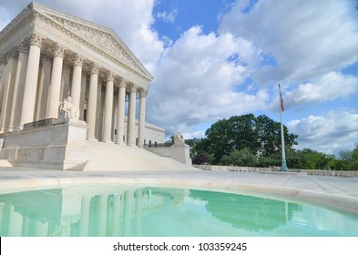 Supreme Court Building with mirror reflection on the pool in a partly cloudy day - Washington DC
