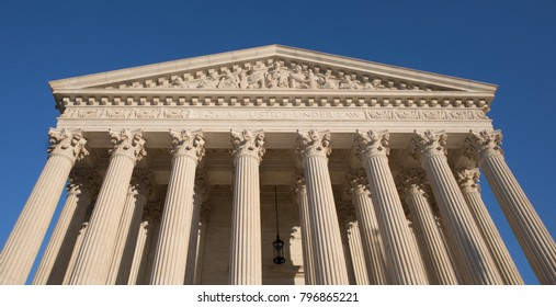 Supreme Court building in Washington, D.C. with bright blue sky.