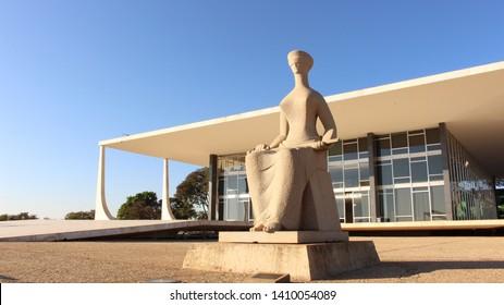 "Supreme Federal Court (STF) building in Brasília-DF, Brazil, designed by Oscar Niemeyer. ""The Justice"" sculpture, by Alfredo Ceschiatti in front of the STF. Brasília/DF/Brazil - 08/28/2018"
