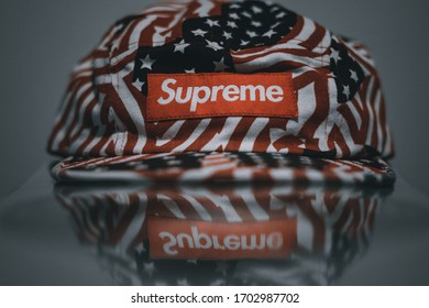 Supreme hat over a reflective surface