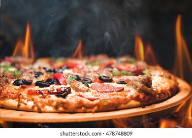 Supreme meat and vegetable pizza on stone in wood-fired oven with open flames