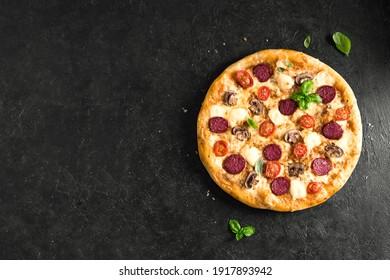 Pizza Suprême au pepperoni, champignons et fromage mozzarella sur table noire, vue de dessus, espace pour copie. Des pizzas fraîches faites maison.